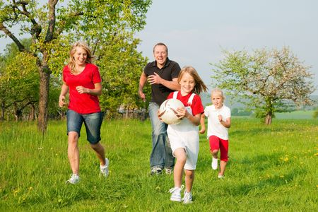 outdoor sports: Happy family playing football, one child has grabbed the ball and is being chased by the others Stock Photo