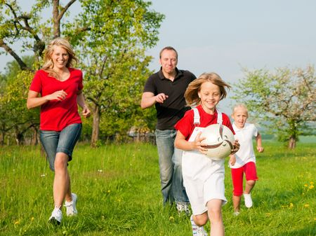 Happy family playing football, one child has grabbed the ball and is being chased by the others Stock Photo - 6117172