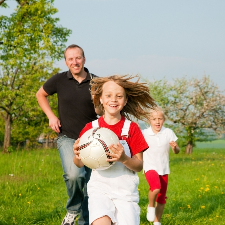 father children: Happy family playing football, one child has grabbed the ball and is being chased by the others Stock Photo