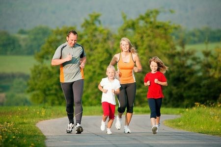 Family doing sport by jogging outdoors with the kids in a beautiful summer landscape in the late afternoon sun photo
