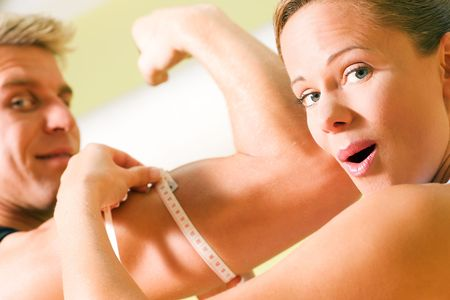 circumference: Woman measuring rather impressive circumference of arm with muscles of her guy