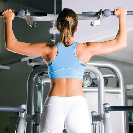 pullups: Beautiful woman doing pull-ups on a machine in the gym