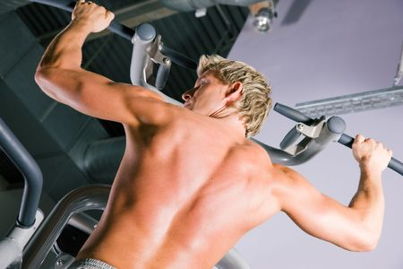 Strong man doing pull-ups on a machine in the gym photo