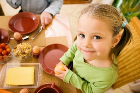 meisje eten: Klein meisje eten ontbijt of diner met haar familie