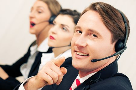 Group of three customer care representatives in a call center with headphones Stock Photo - 6117270