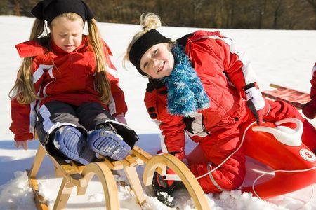 toboga: Due bambini piccoli con loro lo slittino in cima ad una collina nella neve in attesa di iniziare il divertimento