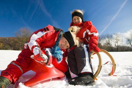 toboga: Due piccoli bambini con le loro piste per slittini in cima ad una collina nella neve in attesa di iniziare il divertimento