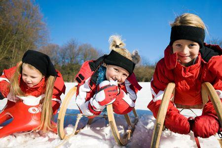 toboga: Tre piccoli bambini con loro lo slittino in cima ad una collina nella neve in attesa di iniziare il divertimento