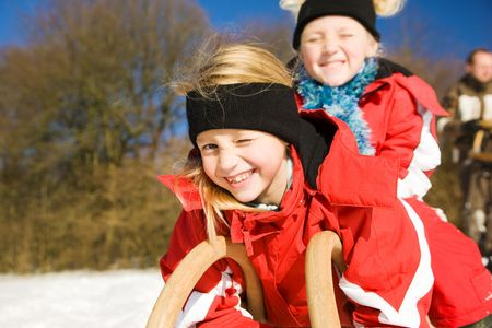 toboggan: Two little children with their toboggan at the top of a hill in the snow waiting to start the fun