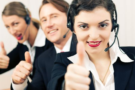 Group of three customer care representatives in a call center with headphones, all showing thumbs up photo
