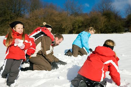Family with kids having a snowball fight in winter on top of a hill in the snow Stock Photo - 6117263