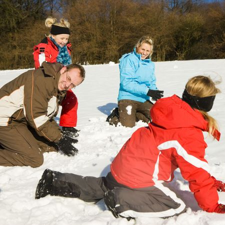 Family with kids having a snowball fight in winter on top of a hill in the snow photo