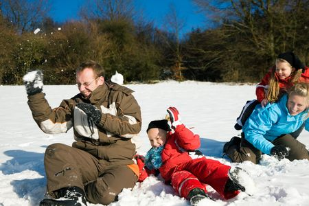 boule de neige: Family with kids having a snowball fight in winter on top of a hill in the snow
