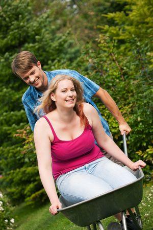 Man carrying his girl in a wheelbarrow through their garden photo