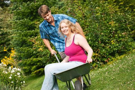 Man carrying his girl in a wheelbarrow through their garden photo