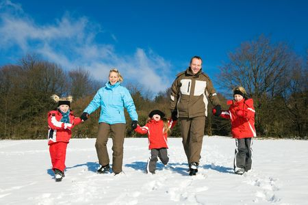 walk in: Active family having a winter walk in the snow Stock Photo