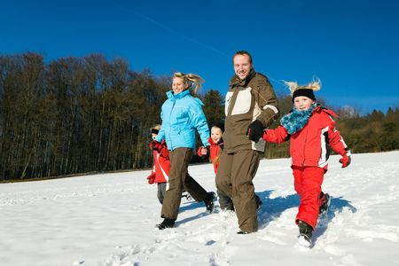 Active family having a winter walk in the snow photo