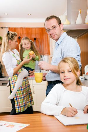 routines: Everyday life of a family - kids doing their homework in the kitchen before going to school