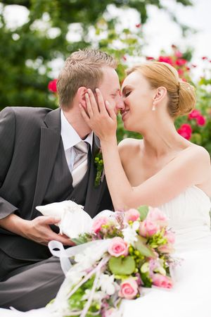 Wedding - groom kissing the bride in a park, he is holding the rings, roses in the background photo