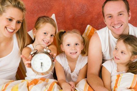 levantandose: Familia en la cama en la ma�ana, en una met�fora de la ? de reloj para levantarse disfrutar el d�a de celebraci�n de ni�o