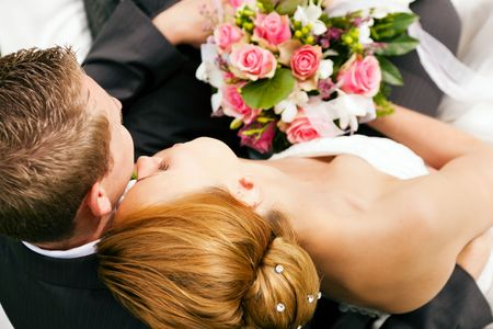 wedding couple hugging and kissing, the bride holding a bouquet of flowers in her hand photo