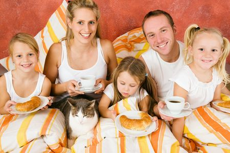 breakfasting: Family of five and their cat having breakfast in their bed in the morning