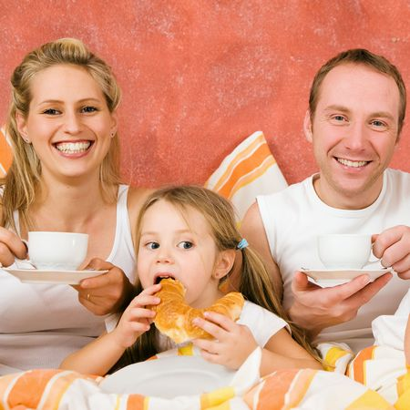breakfasting: Family having breakfast in their bed in the morning