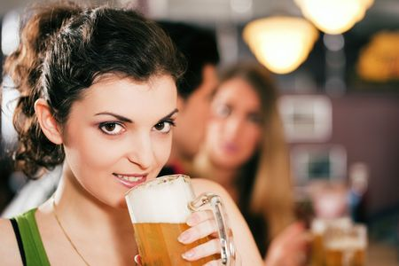 Group of three friends in a bar drinking beer - selective focus on beautiful woman in front zipping from her glass photo