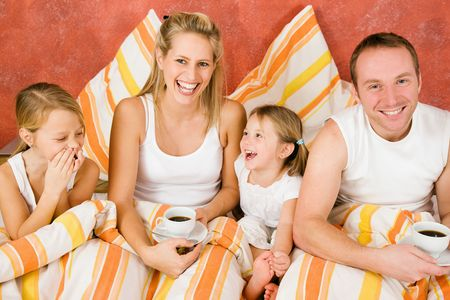 Family having breakfast in their bed in the morning photo