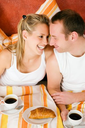 Couple having breakfast in bed in the morning looking at each other being happy and smiling photo
