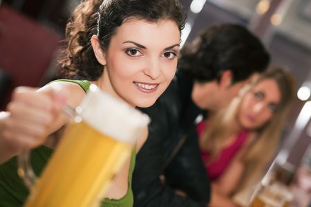 Group of three friends in a bar drinking beer - selective focus on beautiful woman in front pointing her glass at the viewer photo