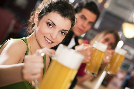 after the party: Group of three friends in a bar drinking beer - selective focus on beautiful woman in front pointing her glass at the viewer Stock Photo