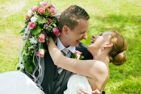 Visibly happy newlywed couple - the groom is carrying the bride Stock Photo - 6133611