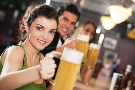 Group of three friends in a bar drinking beer - selective focus on beautiful woman in front pointing her glass at the viewer Stock Photo - 6133598