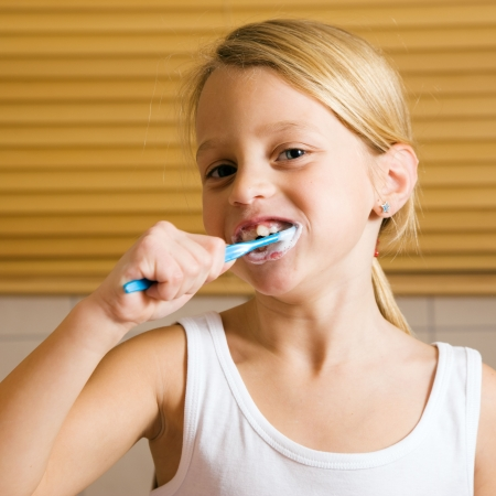 Child brushing her teeth with a hand toothbrush to get ready for bed time  photo