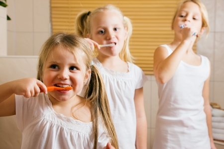 brushing: Children brushing their teeth with a hand toothbrush to get ready for bed time