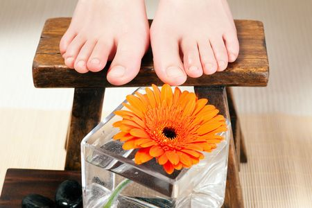 footstool: Feet in a wellness setting sitting on a footstool Stock Photo