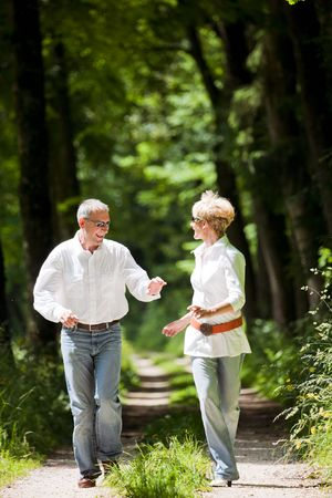 Mature or senior couple deeply in love chasing each other in late spring or early summer photo