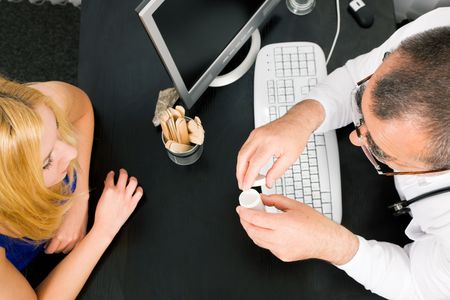 adverse reaction: Young woman consulting her doctor, he has a prescription drug bottle in his hand Stock Photo