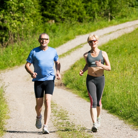 jogging in nature: Mature or senior couple doing sport outdoors, jogging