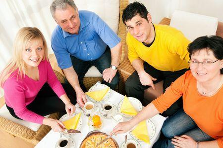 the offspring: Familia (padres y adulta de la descendencia) con caf� y pastel junto Foto de archivo