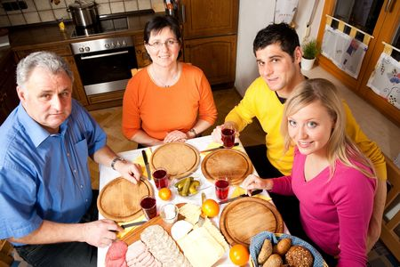 cold cut: Family with adult kids having a meal with bread, cold cuts, and cheese