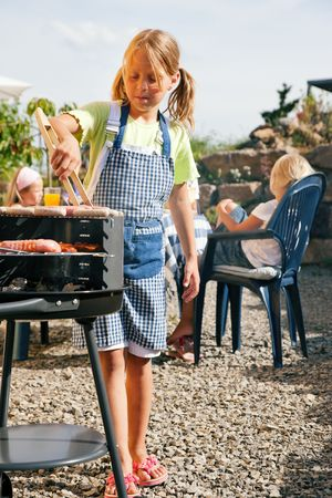 Family having a barbecue party - little kid at the barbecue grill preparing meat and sausages photo