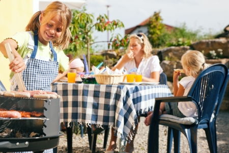 Family having a barbecue party - little kid at the barbecue grill preparing meat and sausages Stock Photo - 6171491