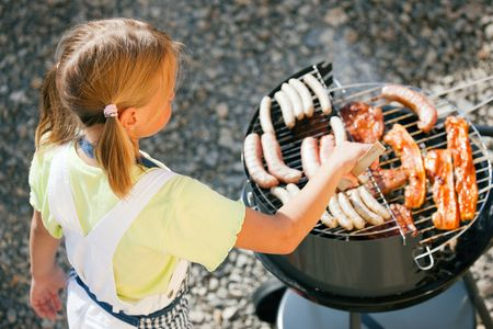 Little girl preparing meat and sausages using a barbecue grill Stock Photo - 6171499