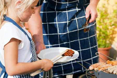 Father and daughter preparing meat and sausages using a barbecue grill Stock Photo - 6171497