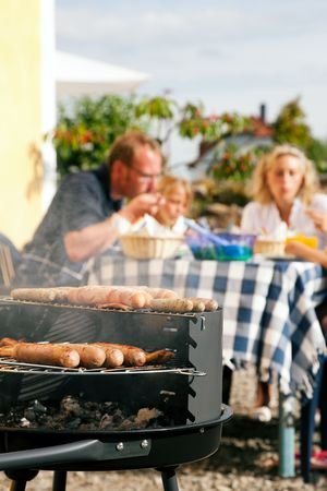 garden party: Family having a barbecue in the garden, eating (focus on barbeque grill!) Stock Photo