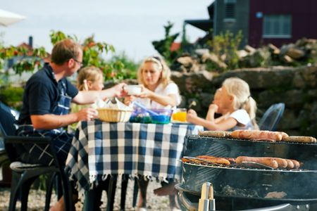 Family having a barbecue in the garden, eating (focus on barbeque grill!) photo