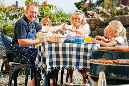 family dinner: Family having a barbecue in the garden, eating Stock Photo