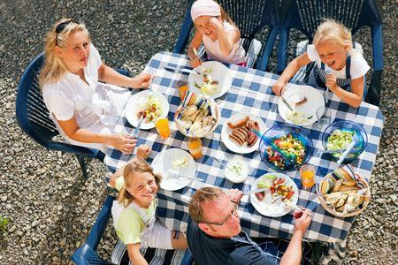 fiesta familiar: Familia tener cena en su jard�n - cosas de barbacoa y ensalada Foto de archivo